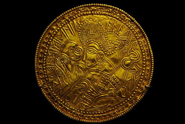 A Migration Period Germanic gold bracteate featuring a depiction of a bird, horse, and stylized head wearing a Suebian knot sometimes theorized to represent the Germanic god Wōden. As the Roman Empire began to decline there were several migrations into their territory by Germanic tribes and the Huns, people the Romans called barbarians. (Bloodofox/CC BY SA 3.0)