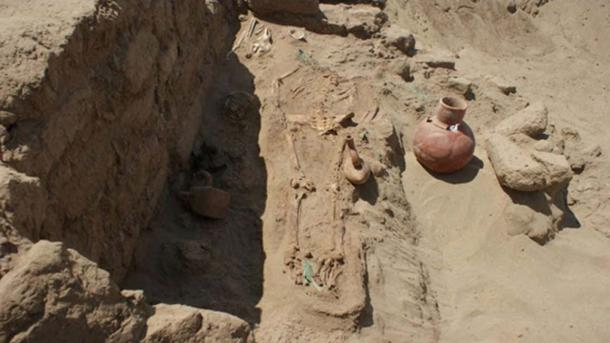 A Moche grave with the remains of a woman and a child and grave goods. (Deisy Cubas)