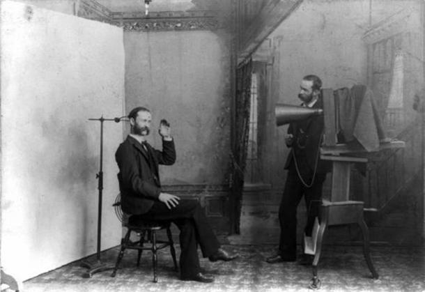 A composite photograph from 1893 showing a photographic studio interior. One man is seated on a stool near an adjustable clamp to hold his head steady during a long portrait exposure. The second man, standing next to a large view camera, looks like the person being photographed. (Public Domain)