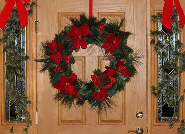 A door decorated with a Christmas wreath.