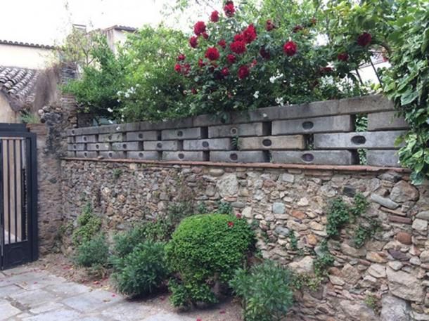 A garden wall featuring inscribed plaques.  (©Elyn Aviva)