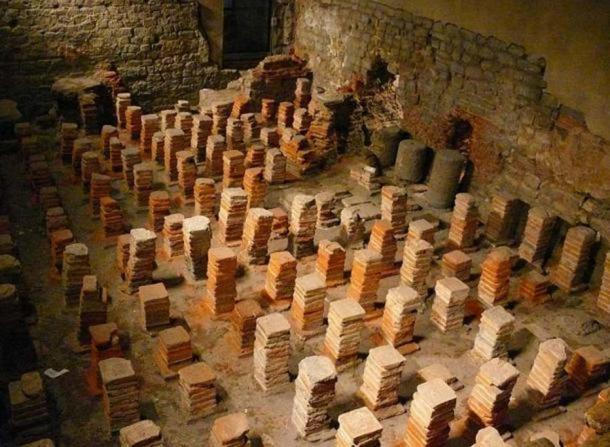 """A hypocaust (Latin hypocaustum) in the Roman Baths, Bath, UK. A hypocaust is an ancient Roman system of central heating. The word literally means """"heat from below"""", from the Greek hypo meaning below or underneath, and kaiein, to burn or light a fire."""
