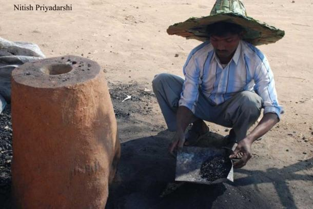 A modern Asur man using a traditional furnace to make iron in Ranchi city.