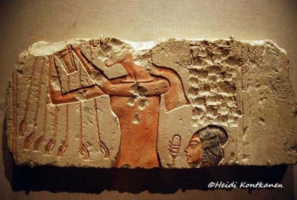 A painted limestone block from Tell el-Amarna shows Akhenaten presenting a bouquet to the Aten; while his daughter, Meritaten, who wears her hair in an elaborate plaited sidelock symbolizing youth, shakes a sistrum. Brooklyn Museum, New York.