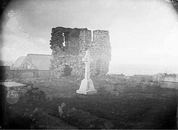 Abbey ruins with graves and Celtic cross memorial, circa 1885.