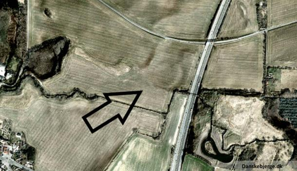 Aerial photo of Vallø Borgring. This is an edited version of a satellite photo with added hill shade. The arrow is pointing at a site which has a clear circular form.