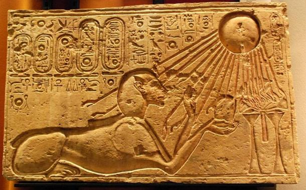 This stone relief of the ancient Egyptian city of Amarna shows Akhenaten as a sphinx with Aten the sun god illuminating him and his offering.