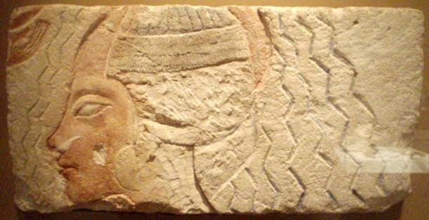 An Amarna relief depicting a woman undergoing a purification ritual. While the figure has been recarved, the large earings and style of wig are thought to be representative of Queen Kiya.