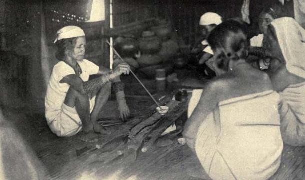 An Itneg shaman renewing an offering to the spirit shield (1922, Philippines). (Public Domain)
