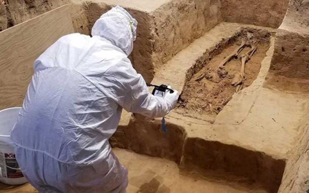 An archaeologist investigates the burial while wearing a suit that will minimize contamination to the historical site. (Jamestown Rediscovery)