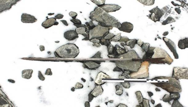 An arrow from 800 AD found on the ground, partly covered by snow.