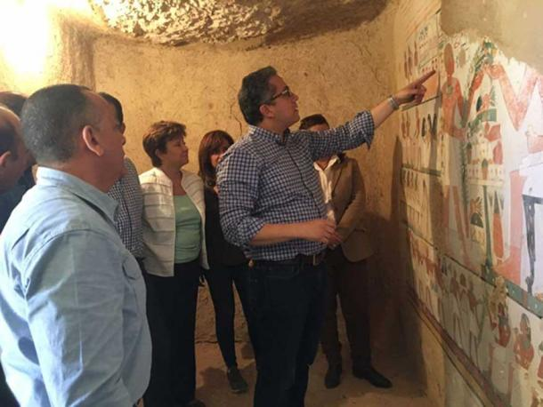An inspection of the painted walls in one of the newly-discovered tombs. Credit: Ministry of Antiquities