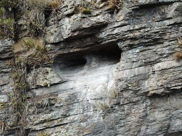 An opening in the cliff face appears to be hewn