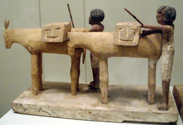 Ancient Egyptian tomb figurines depicting workers loading up a couple of donkeys with supplies. Early Middle Kingdom, circa 2000 BC.