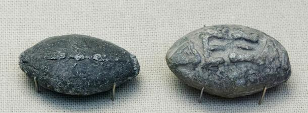 """Ancient Greek sling bullets with engravings. One side depicts a winged thunderbolt, and the other, the Greek inscription """"take that"""" in high relief."""