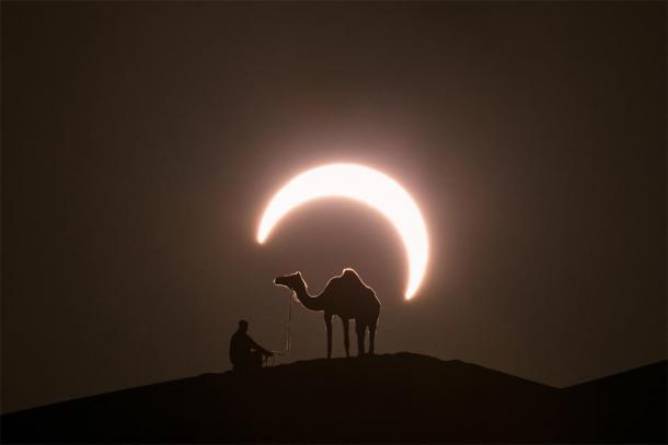 Annular solar eclipse in desert with a silhouette of a dromedary camel. Liwa desert, Abu Dhabi, United Arab Emirates. (Kertu / Adobe Stock)