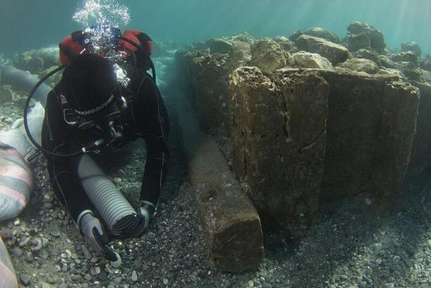 Archaeologist documenting wooden caisson