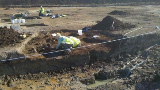 Archaeologists at work in the waterlogged pit. (Oxford Archaeology)