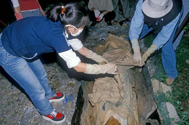 Archaeologists in Andong City, South Korea, unwrap cloth covering the 16th-century mummy of Eung-tae, a member of Korea's ancient Goseong Yi clan.
