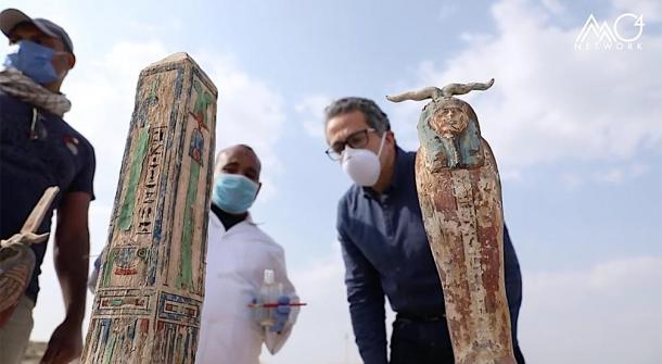 Archaeologists and Khaled El-Enany inspect the ancient Egyptian obelisk and another figurine unearthed at the Saqqara archaeological site. (Egypt's Ministry of Tourism and Antiquities)