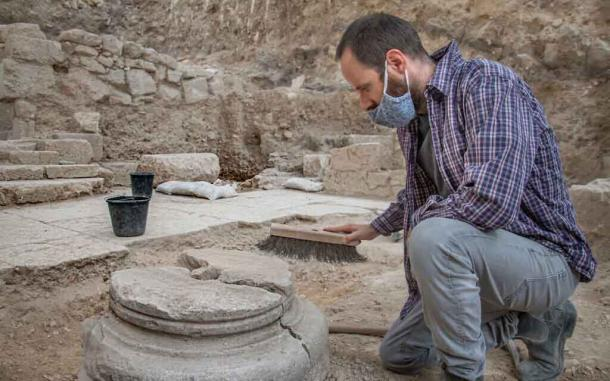 An archaeologist cleaning one of the pillar bases upon which the 1,500-year-old Byzantine church was built. The church was found in the garden area before the ritual bathes were discovered. (Yoli Schwarz / Israel Antiquities Authority)