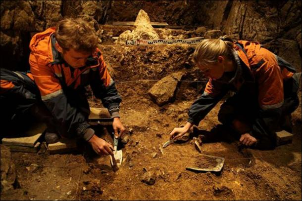 Archeologists working inside the eastern gallery of the Denisova Cave.