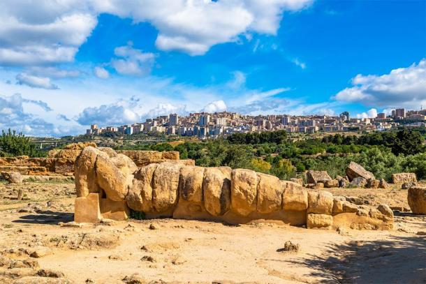 The statue of Atlas lying down with the modern Italian city of Agrigento in the background. (javarman / Adobe Stock)