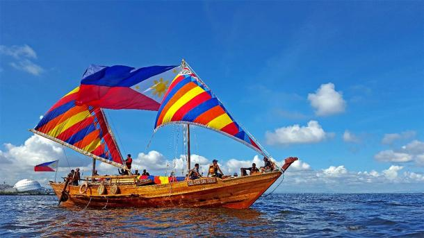 Balangay boat in the waters of Manila Bay with large Philippine flag (Fung360 / CC BY-SA 4.0)