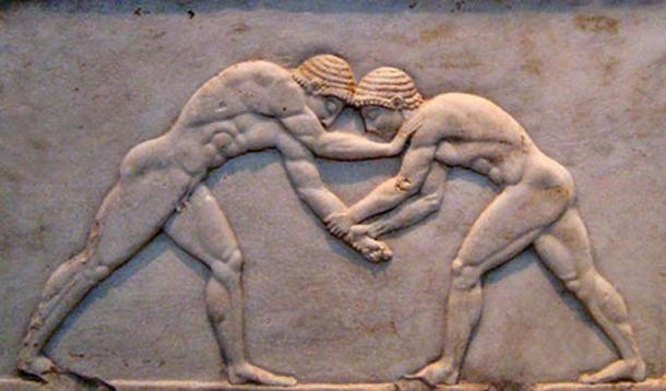 """Base of a funerary kouros found in Athens, built into the Themistokleian wall. Three sides are decorated in relief: wrestlers are on the front side, an unspecified athletic game (known as """"Ball Players"""")"""