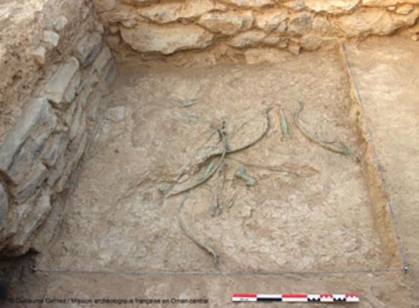 Bows, arrows, daggers and axes scattered on the ground at Mudhmar East, Oman.