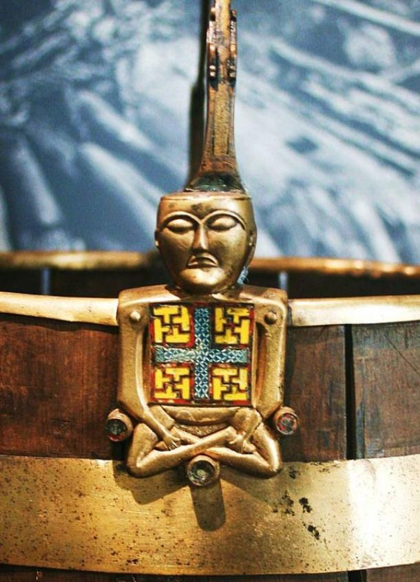 """A curious artifact, the so-called """"Buddha bucket"""" (Buddha-bøtte), a brass and cloisonné enamel ornament of a bucket (pail) handle in the shape of a figure sitting with crossed legs.  It is thought this item likely came from Ireland, and might have been taken during a raid."""