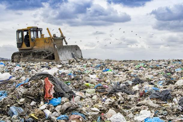Bulldozer working to move waste showing the buildup of plastic on our planet. (Perytskyy / Adobe stock)
