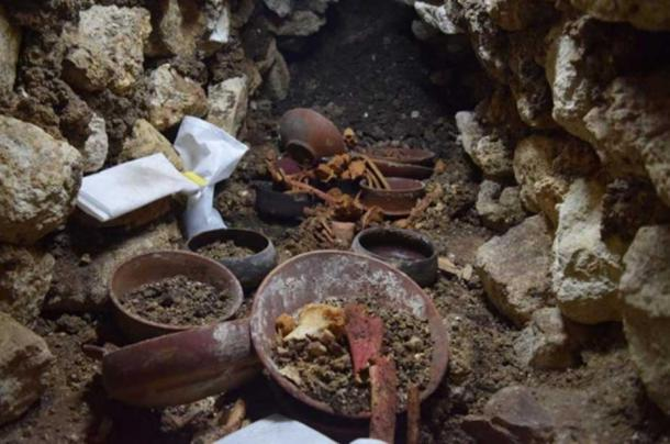 Burial 80 during excavation shows a stone cup in the center surrounded by bones