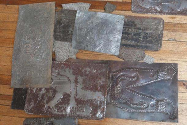 Carved metallic plates from Father Crespi's collection strewn on the floor in a dilapidated old building.