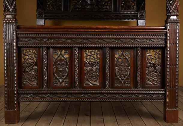 Carved portraits on the foot board of the antique bed. (The Langley Collection)
