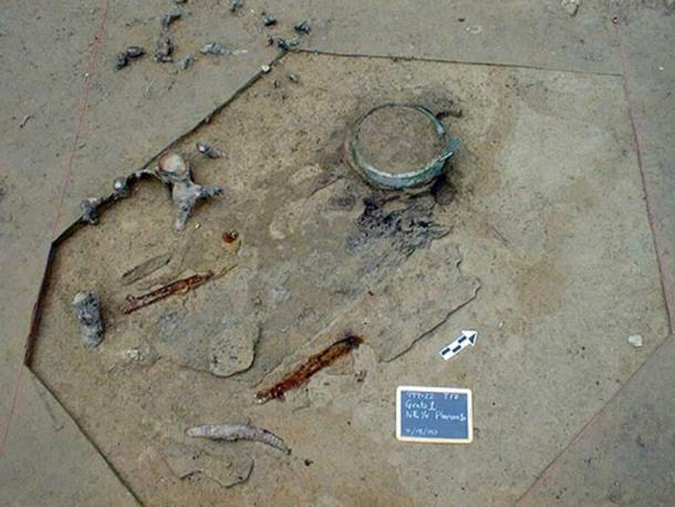 Cauldron, iron spears, sword and helmet attachment found in the burial chamber.