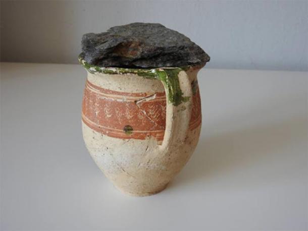 Ceramic mug covered with stone, where the coin hoard was found. (KPÚ Košice)