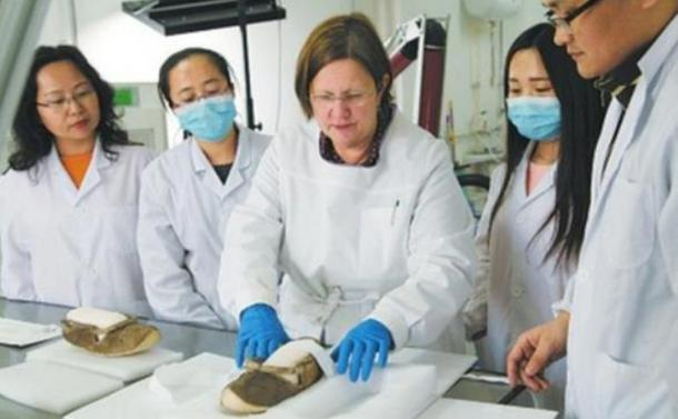 A Chinese archeological research institute restoring a pair of 1,400-year-old shoes unearthed from the Astana Tombs.