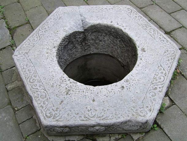 A Chinese carved stone well head.