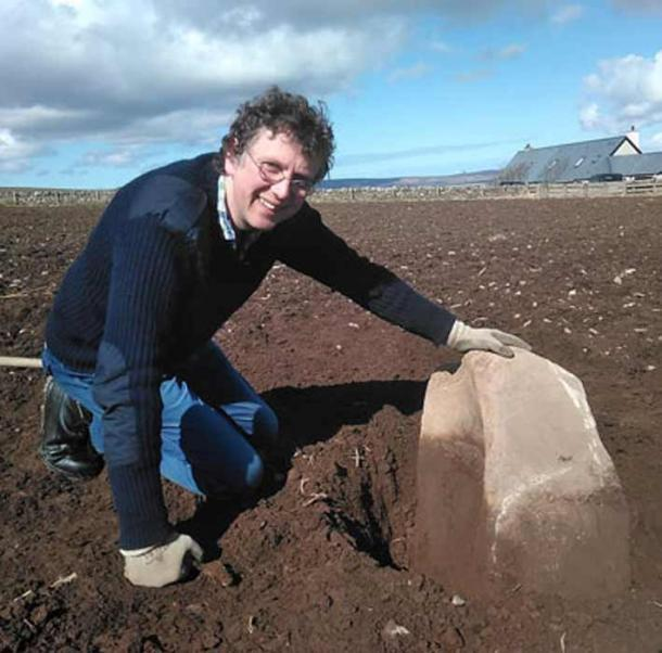 Chris Gee, from the Orkney Research Centre for Archaeology (ORCA), with the massive saddle quern revealed by ploughing earlier this month. (Ragnhild Ljosland / Archaeology Orkney)