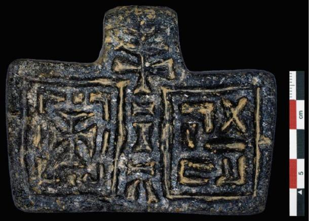 """A Christian stone pendant found in the basilica with a cross on the left and, on the right, the word """"venerable"""" in Ge'ez – an ancient Ethiopian language, which remains the liturgical language of the Ethiopian Orthodox Church. (Credit: I. Dumitru via Antiquity)"""