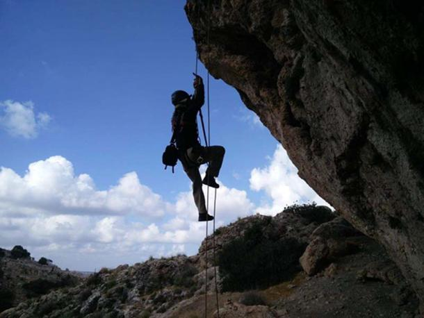 Climbing with ropes to reach the cave. (Image: Yoav Negev, courtesy Israel Antiquities Authority)