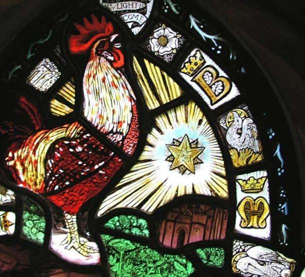 Close up of the Epiphany Window, showing the double star, the rooster, the phoenix, and the letters B and M. The red-brick arch can be seen directly below the star.
