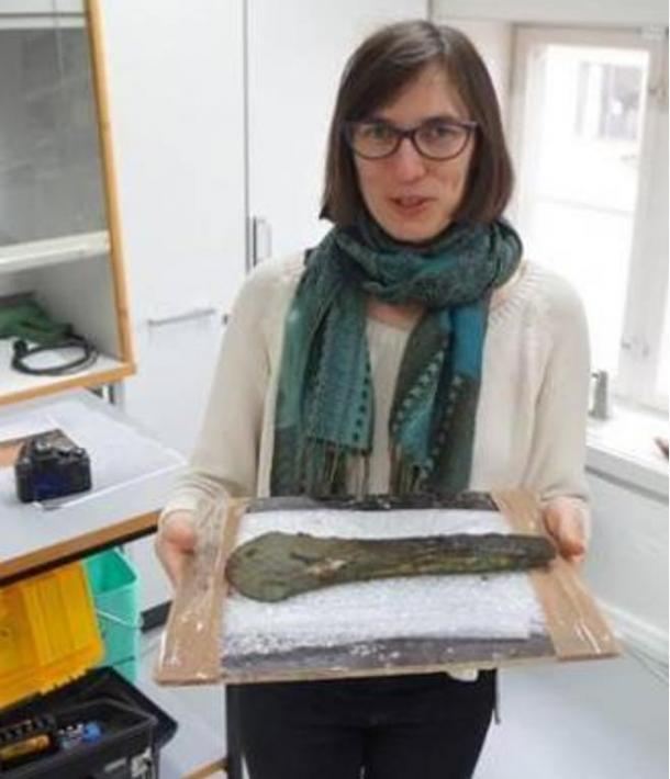 Constanze Rassman holding one of the bronze axes found at the site. 2015.