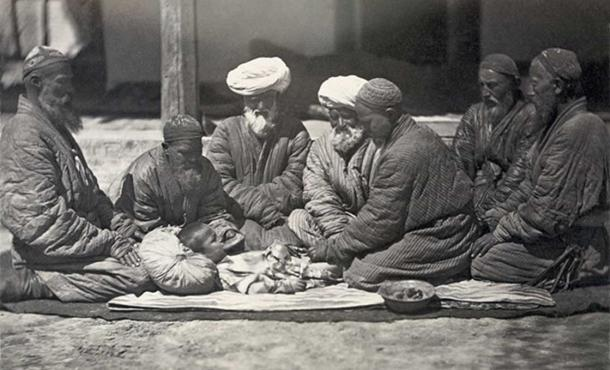 """Customs of Central Asians. Circumcision."" ""Photograph shows a group of men seated on the ground near a small boy who is being circumcised."" (Public Domain)"