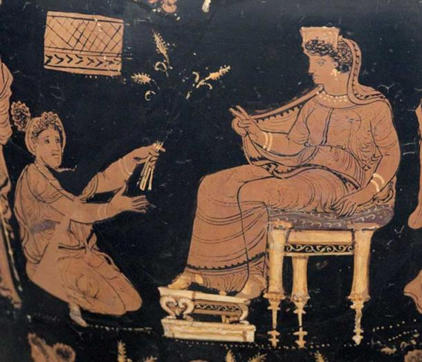 Demeter, enthroned and extending her hand in a benediction toward the kneeling Metaneira who offers the triune wheat that is a recurring symbol of the mysteries