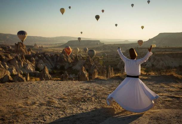 Dervish doing a ritual in Cappadocia with balloons in the background at sunrise.