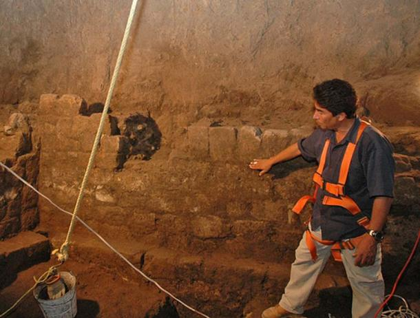 Director of the excavation, Sergio Gomez, inspects a portion of a stone wall found throughout the tunnel. A high water mark that covers the entire tunnel and cavern area are evidence that water was an important ingredient in some chemical reaction.