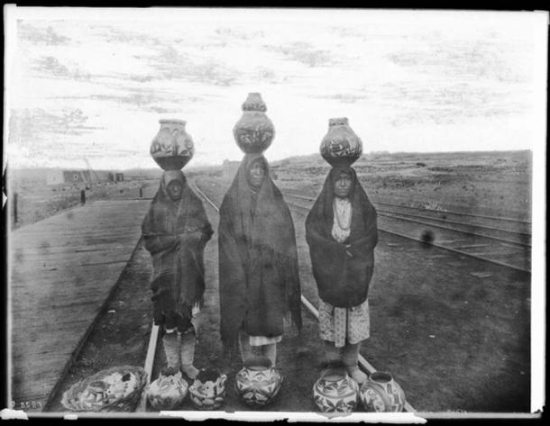 Disparity of wealth created by the different societies in a nation. Three Pueblo Indian women displaying their ollas for sale at the railroad tracks, New Mexico