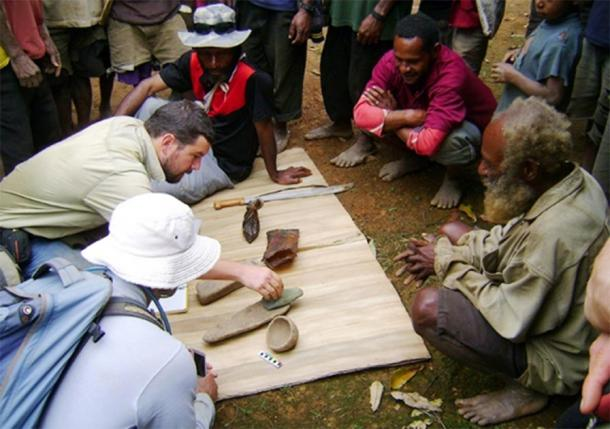 Dr Ben Shaw and some locals examine a few of the Papua New Guinea artifacts unearthed at the Waim dig site in the northern highlands. (UNSW / Ben Shaw)